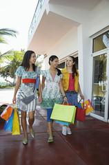 Three teenage girls 16-17 carrying shopping bags, walking on street