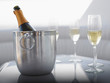 Flutes and champagne in ice bucket on table