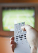 Man adjusting TV channel volume with remote control, close-up of hand