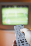 Man changing TV channel with remote control, close-up on hand