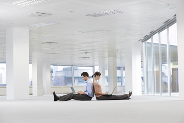 Man and Woman Using Laptops in Empty Office Space