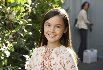 Girl smiling, head and shoulders, mother locking door in background