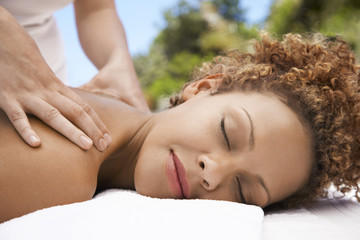 Woman receiving massage, head and shoulders, eyes closed