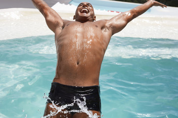 Man in diving backwards into swimming pool, smiling, half length