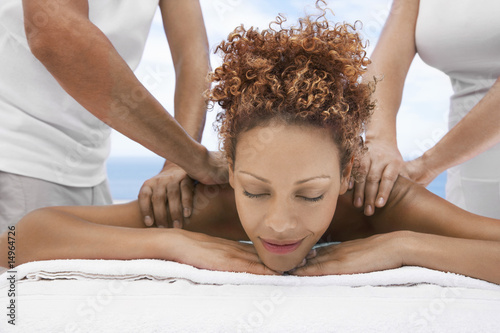 Woman receiving massage from two people, head and shoulders, eyes closed