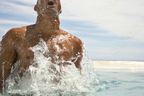 Man surfacing in swimming pool, half length, cropped