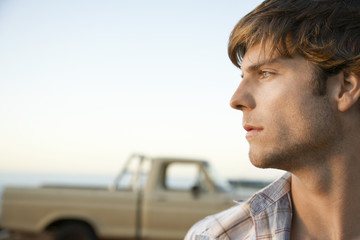 Young man, head and shoulders, profile, in front of van