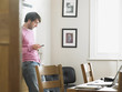 Man standing in kitchen, text messaging