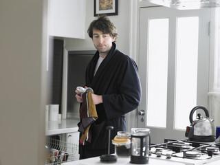 Man standing in kitchen, empting dishwasher
