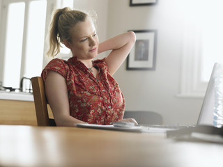 Woman using laptop sitting at dining table, low angle view