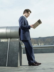 Young man in suit leaning on pipe outdoors, reading paper, side view