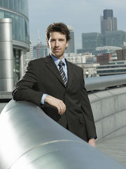 Young businessman leaning on pipe outside building