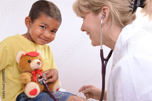 female doctor examining little child boy
