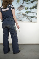 Artist looking at painting, back view