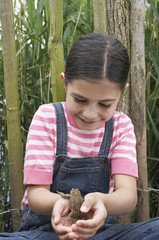 Girl 5-6 holding toad by fence