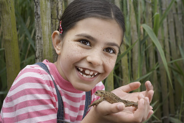 Girl 5-6 holding toad by reeds