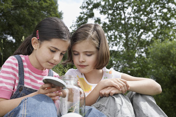 Two girls 7-9 examining jar of insects, outdoors