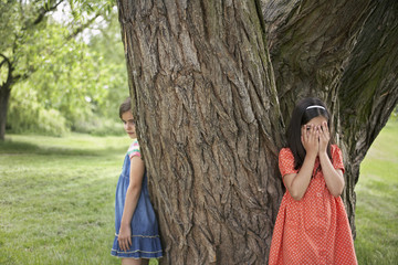 Two girls 7-9 playing hide and seek by tree