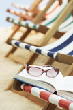 Row of deck chairs on beach, book with sunglasses in foreground