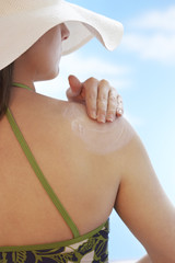 Woman applying sunscreen to shoulder, back view