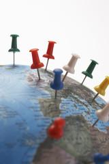 Push pins in various parts of globe, studio shot, close up