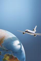 Aeroplane toy next to globe, studio shot