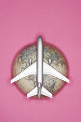 Imitation plane over globe, studio shot, view from above