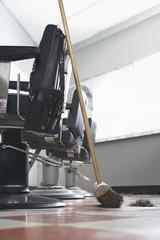 Broom beside barbers chairs