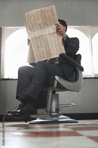 Business man reading newspaper, waiting in barber shop