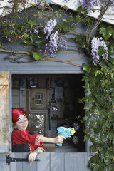 Young boy 7-9 in pirate costume aiming with toy gun from shed
