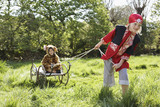 Young boy 7-9 in pirate costume pulling boy 5-6 in jaguar costume sitting on cart, smiling