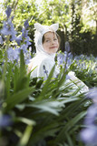 Portrait of young girl 5-6 sitting in flowers in horse costume