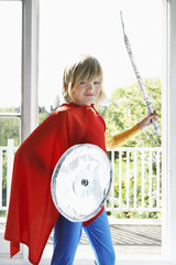 Portrait of young boy 7-9 in superhero costume holding toy shield and sword, smiling