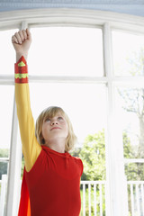 Portrait of young boy 7-9 in superhero costume with raised fist, looking up