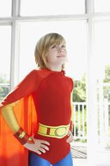 Portrait of young boy 7-9 in superhero costume, hands on hip, indoors