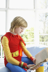 Young boy 7-9 in superman costume, sitting and reading indoors