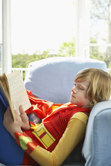 Young boy 7-9 sitting in armchair reading, wearing superhero costume, side view