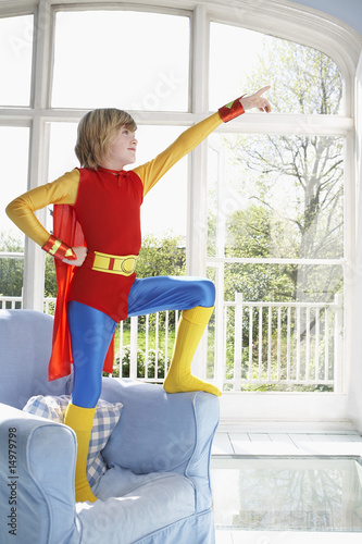 Young boy 7-9 wearing superman costume standing on armchair and pointing