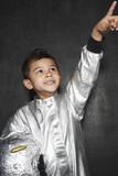 Portrait of young boy 5-6 in astronaut costume, pointing upwards, smiling, studio shot