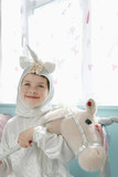 Portrait of young girl 5-6 in unicorn costume holding toy horse, smiling, indoors