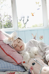 Young girl 5-6 in unicorn costume sleeping on bed with toy horse