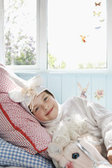 Portrait of young girl 5-6 lying on bed in unicorn costume with toy horse, smiling