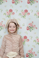 Portrait of young girl 5-6 in bunny costume against wallpaper with floral pattern