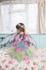 Young girl 5-6 wearing fairy costume sitting on bed by window, back view