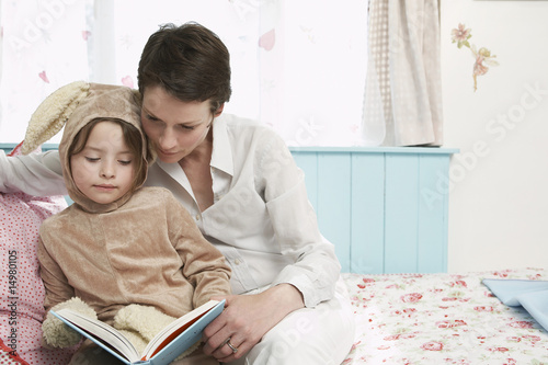 Mother and daughter 5-6 in bedroom reading book, girl in bunny costume