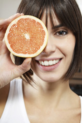 Woman holding half of grapefruit in front of face, portrait, close up