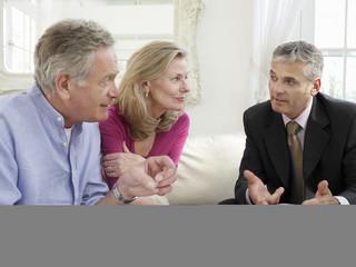 Senior couple sitting on sofa with financial advisor