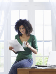 Woman reading document at home