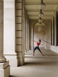 Female athlete throwing javelin in portico