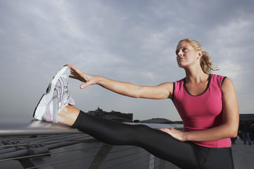 Woman stretching on foot bridge, low angle view